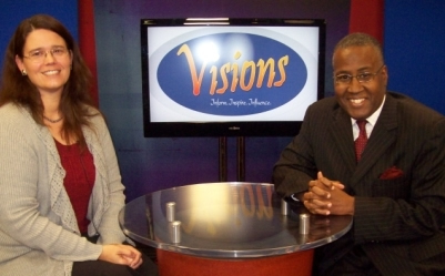 Avalisha Fisher sits next to Cedric Varner in a studio set with the visions logo on a screen behind them.